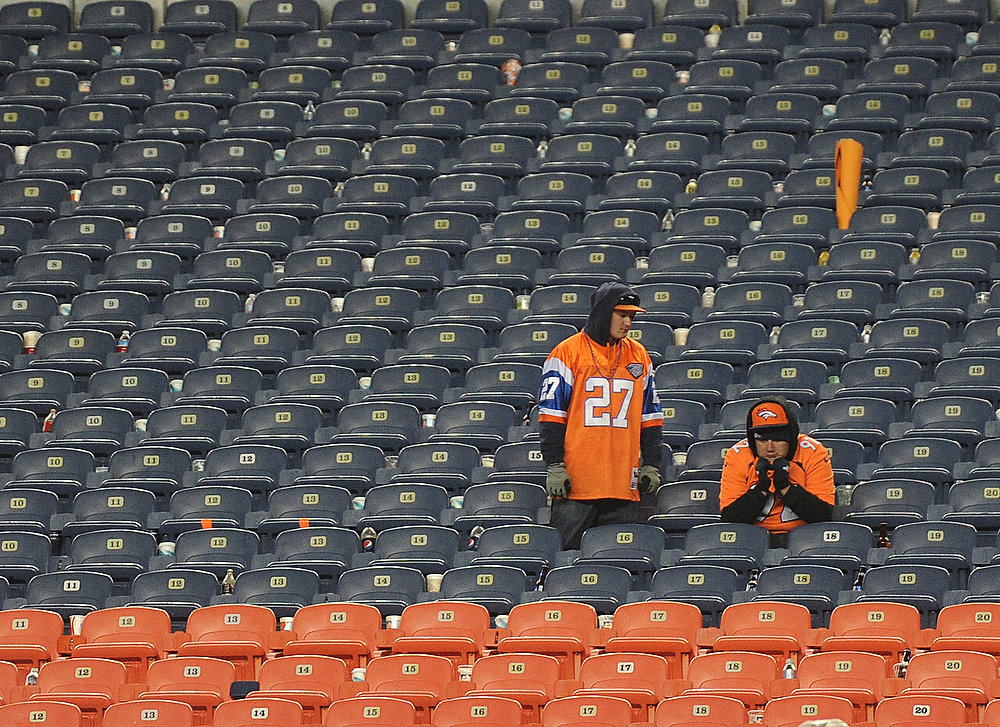 . Broncos fans sit dejected in the stands after they lost to the Ravens in overtime. The Denver Broncos vs Baltimore Ravens AFC Divisional playoff game at Sports Authority Field Saturday January 12, 2013. (Photo by Joe Amon,/The Denver Post)