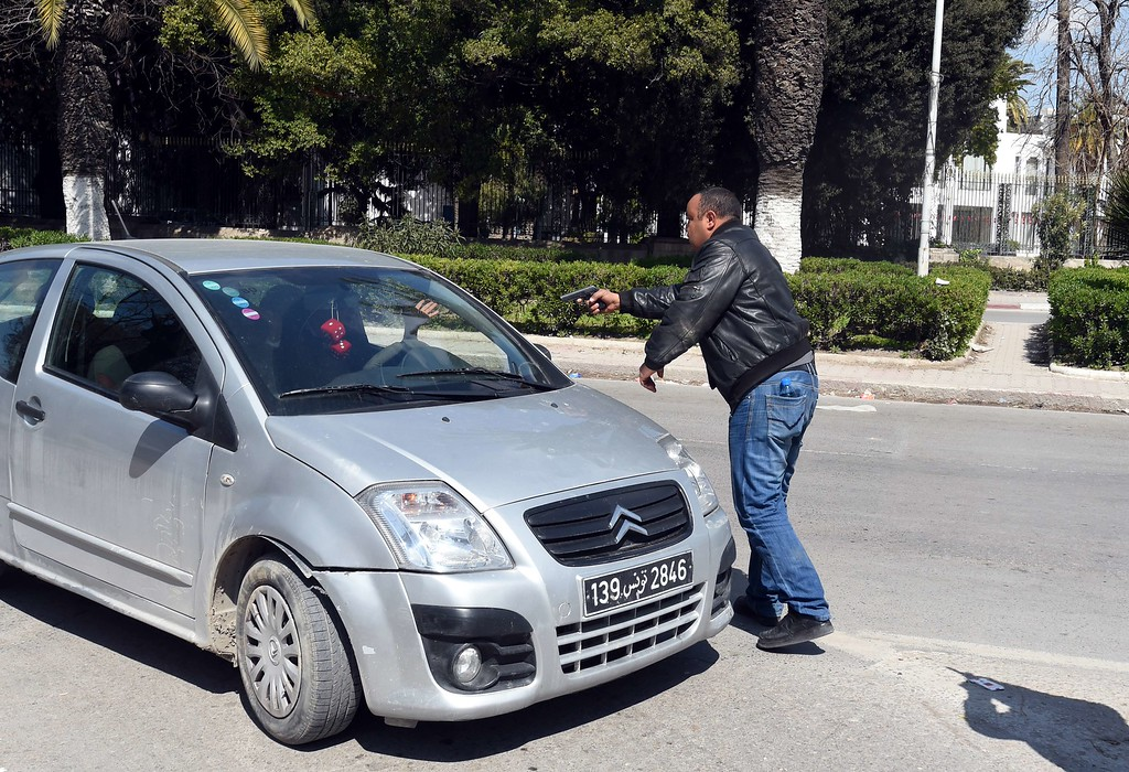 . An armed Tunisian policeman in plainclothes stops a vehicle as security forces secure the area after gunmen attacked Tunis\' famed Bardo Museum on March 18, 2015. At least seven foreigners and a Tunisian were killed in an attack by two men armed with assault rifles on the museum, the interior ministry said. AFP PHOTO / FETHI  BELAID/AFP/Getty Images