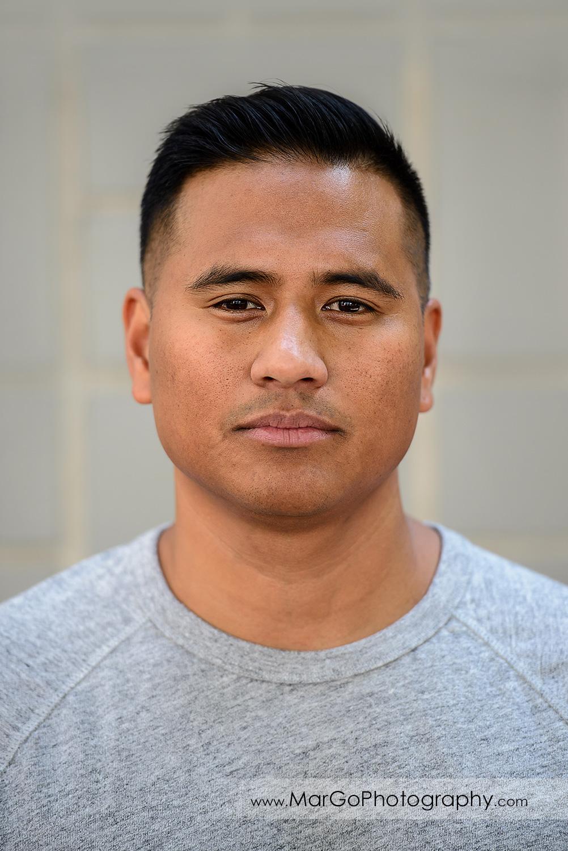 headshot of man in grey T-shirt during engagement session at San Jose San Pedro Square Market
