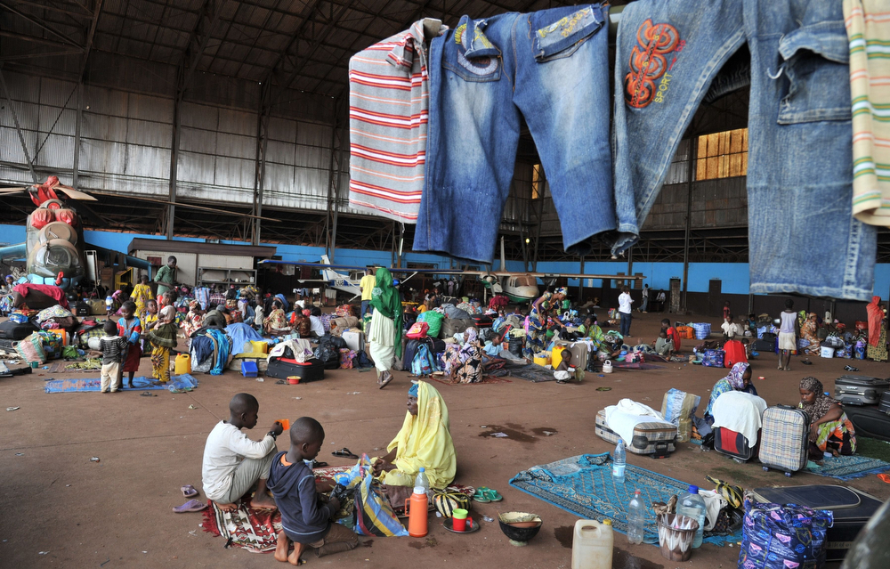 """. Displaced Central African people, Chadians waiting to return home and other refugees, all Muslims, who fled the attacks by Christian extremis militias, sit on January 30, 2014 in a hangar of Bangui airport turned into a refugee camp. Rudimentary weapons taken from Christian extremist militias by French troops in the capital of the Central African Republic were piled up on the ground, near the body of a young man whose ears were ripped off. \""""He was a Muslim from here, named Abaka. They killed him in the courtyard of his house,\"""" a Christian neighbour, Benjamin, told AFP. \""""They\"""" referred to \""""anti-balaka\"""" (anti-machete) vigilantes who fiercely target Muslims in Bangui on the pretext of hunting down ex-rebels from the Seleka coalition.  (ISSOUF SANOGO/AFP/Getty Images)"""