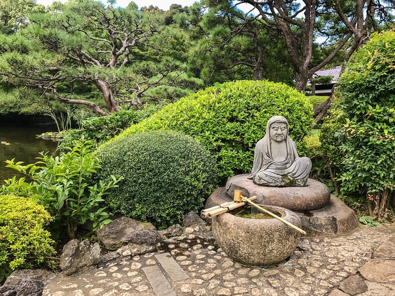 Sitting buddha statue in a Japanese garden.