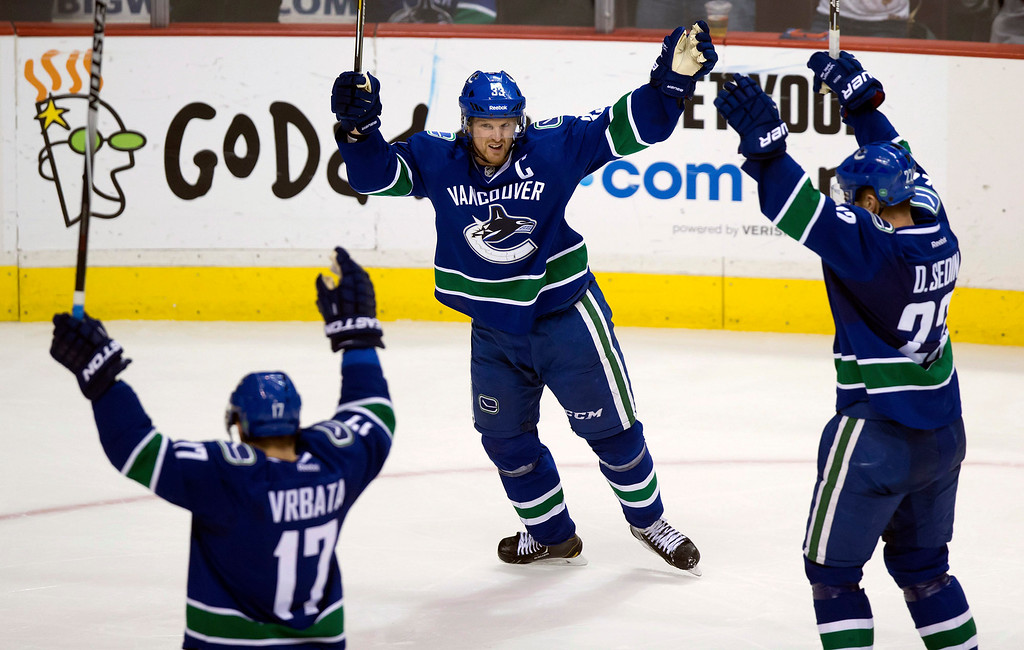 . Vancouver Canucks\' Radim Vrbata, of the Czech Republic, from left, Henrik Sedin, of Sweden, and Daniel Sedin, of Sweden, celebrate Vrbata\'s goal against the Detroit Red Wings during the third period of an NHL hockey game in Vancouver, British Columbia on Saturday, Jan. 3, 2015. (AP Photo/The Canadian Press, Darryl Dyck)
