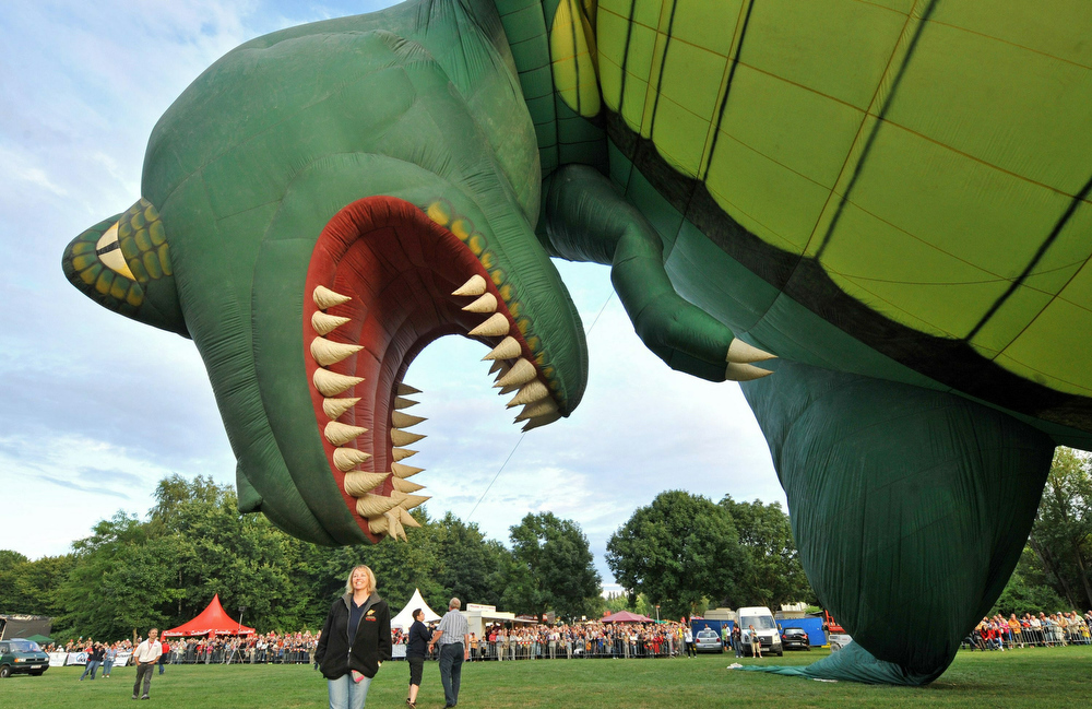 Description of . A dinosaur balloon gets inflated at the 16th Saxonia International Balloon Fiesta in Leipzig, eastern Germany, on July 29, 2010. The hot air balloon festival is running until August 1, 2010.    AFP PHOTO    HENDRIK SCHMIDT