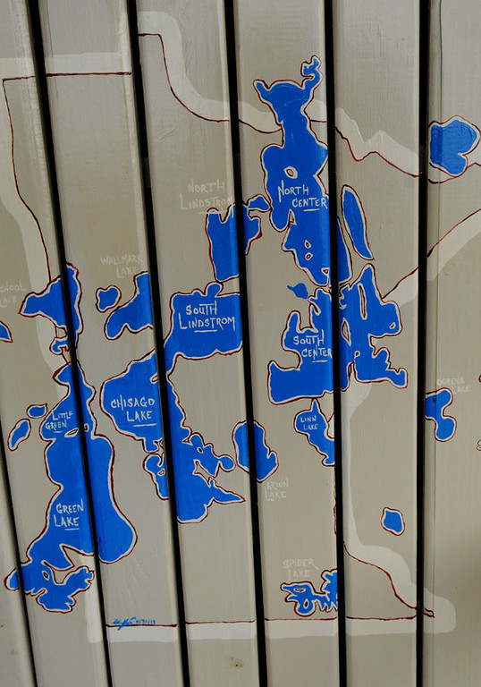 ". A close-up of the ""Chain of Lakes\"" in Minnesota is seen on the  back of an adirondack chair painted by  Boe Krick.  (Pioneer Press: Jean Pieri)"
