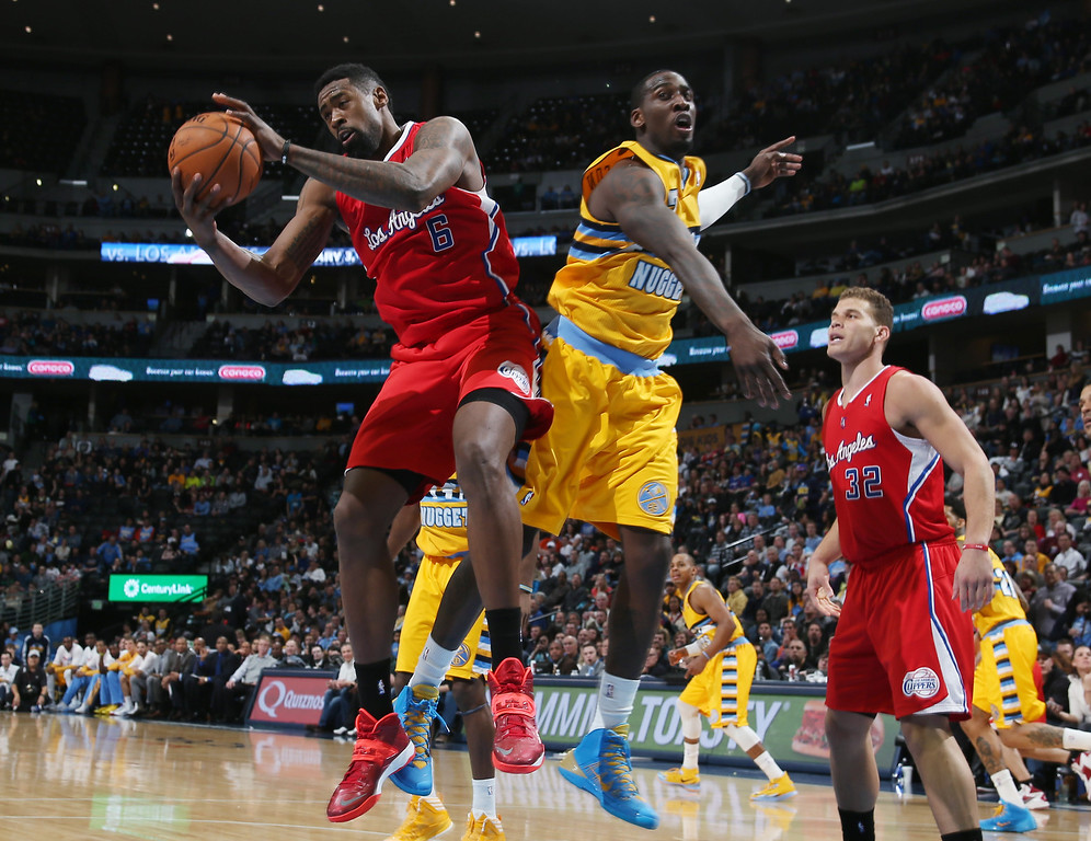 . Los Angeles Clippers center DeAndre Jordan, left, pulls down rebound in front of Denver Nuggets forward J.J. Hickson, center, as Clippers forward Blake Griffin looks on in the third quarter of the Nuggets\' 116-115 victory in an NBA basketball game in Denver, Monday, Feb. 3, 2014. (AP Photo/David Zalubowski)
