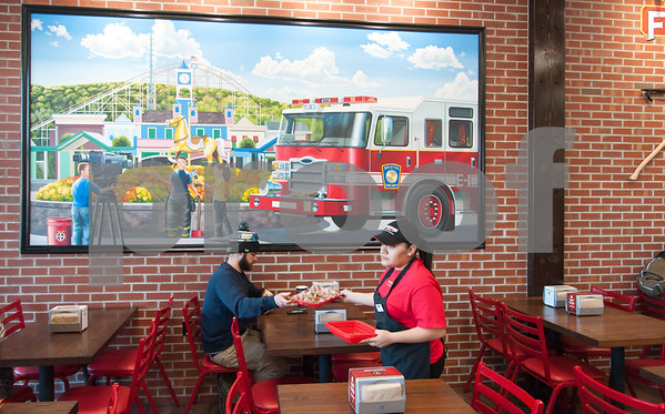 12/11/17 Wesley Bunnell | Staff Firehouse Subs opened for business on Monday at their new location at 594 Farmington Ave. Maria Hernandez takes a tray from a customer as he sits under a large mural of the Bristol Fire Department.