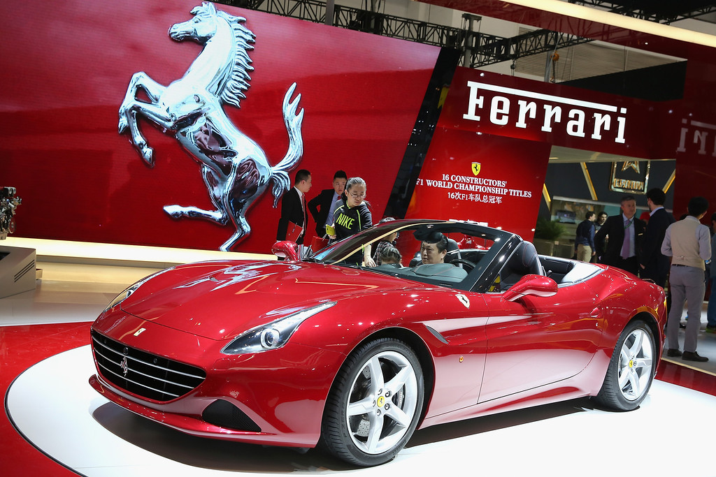 . The potential consumers look at a Ferrairi sport car during the 2014 Beijing International Automotive Exhibition at China International Exhibition Center on April 21, 2014 in Beijing, China. More than 2,000 automotive enterprises from 14 countries and regions participated in the 2014 Beijing International Automotive Exhibition from April 20 to April 29.  (Photo by Feng Li/Getty Images)