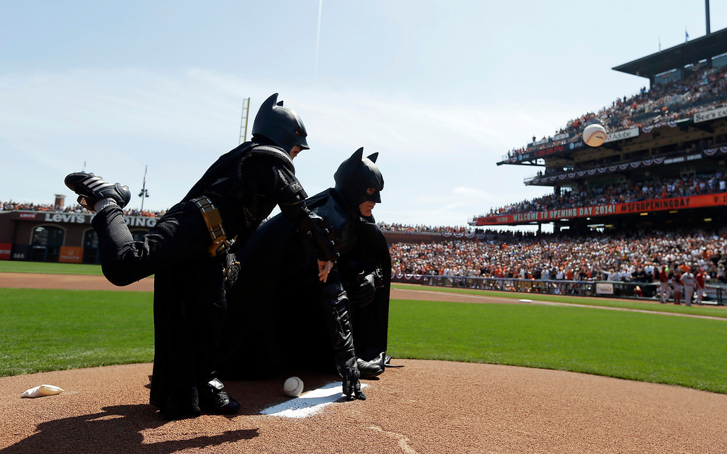 . Miles Scott, left, dressed as Batkid, throws the ceremonial first pitch next to Batman before an opening day baseball game between the San Francisco Giants and the Arizona Diamondbacks in San Francisco, Tuesday, April 8, 2014. On Nov. 15, 2013, Scott, a Northern California boy with leukemia, fought villains and rescued a damsel in distress as a caped crusader through The Greater Bay Area Make-A-Wish Foundation. (AP Photo/Eric Risberg, Pool, File)