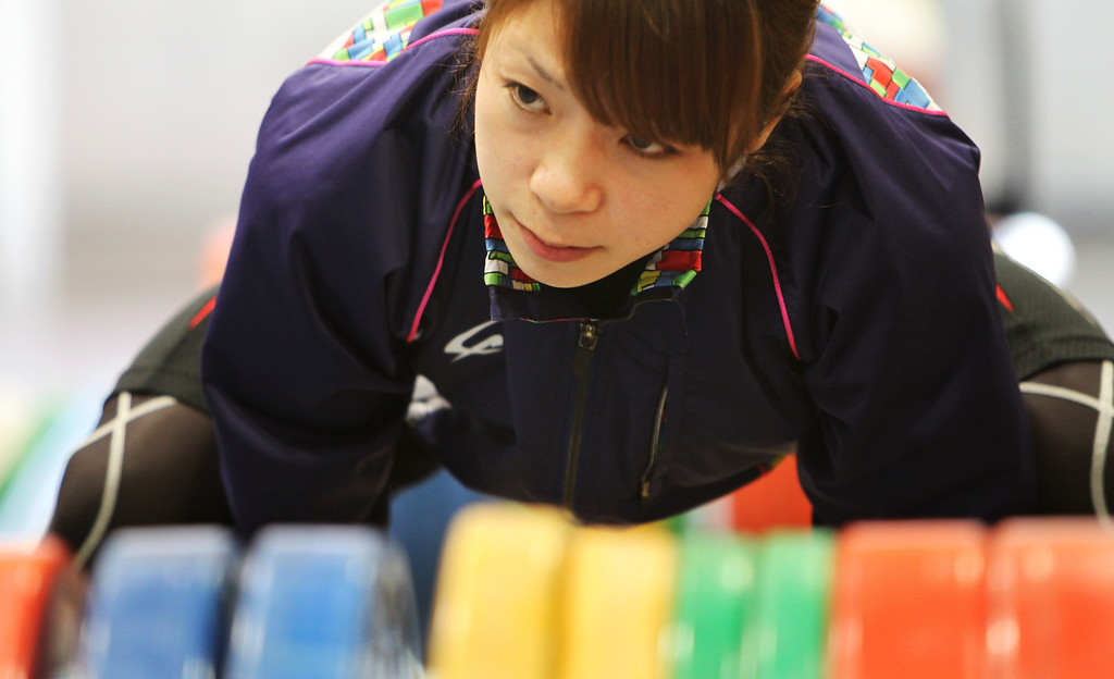 . In this Friday, Aug. 30, 2013 photo, Japanese weightlifter Hiromi Miyake, silver medalist in the London Olympic women\'s 48kg event, warms up before her training at one of Tokyo\'s leading training centers. The Olympics are in Hiromi Miyake\'s blood, a heritage that stretches back to the 1960s, when her uncle won a gold medal at the 1964 Tokyo Games and her father won bronze in Mexico City in 1968. (AP Photo/Junji Kurokawa)
