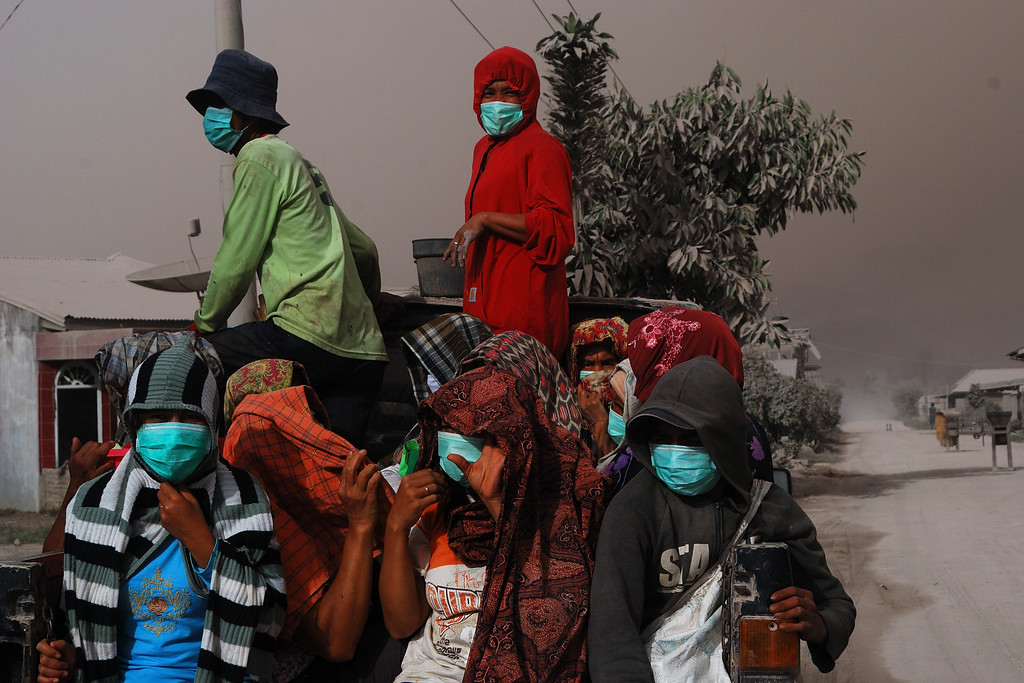 . Residents wearing face masks as protection from volcanic ash evacuate from the eruption of Mount Sinabung volcano seen from Karo district on October 9, 2014.  AFP PHOTO / Sutanta ADITYA/AFP/Getty Images