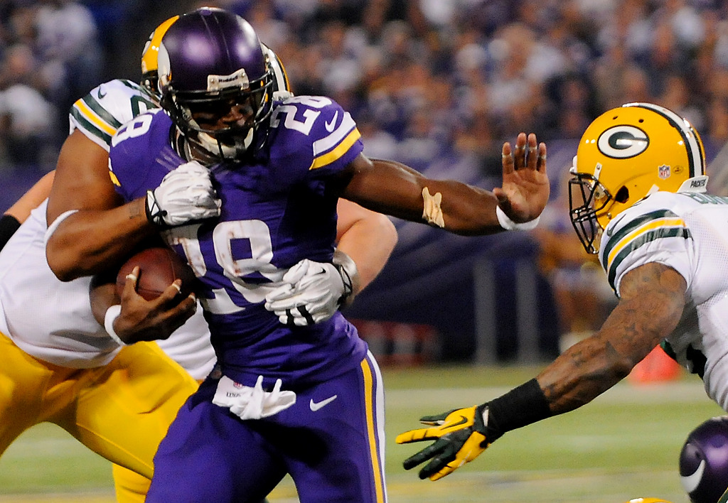 . Minnesota running back Adrian Peterson stiff-arms Green Bay strong safety Morgan Burnett as outside linebacker Mike Neal tries to bring him down in the second quarter. (Pioneer Press: John Autey)