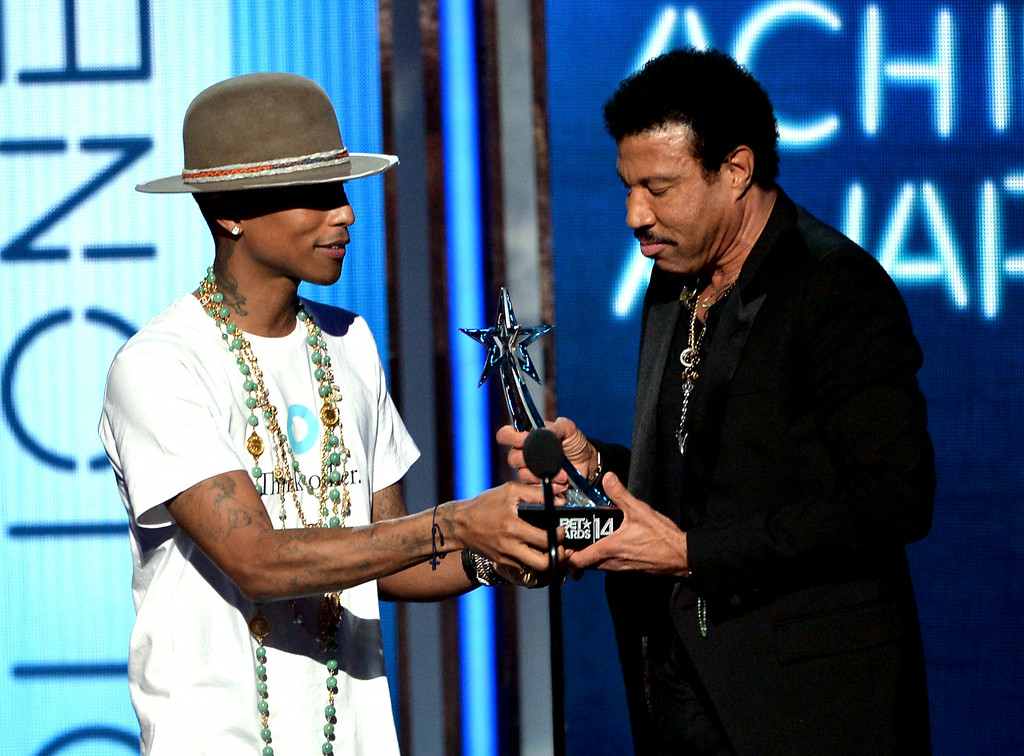 . Singer Lionel Richie (R) accepts the 2014 BET Lifetime Achievement Award from singer Pharrell Williams onstage during the BET AWARDS \'14 at Nokia Theatre L.A. LIVE on June 29, 2014 in Los Angeles, California.  (Photo by Kevin Winter/Getty Images for BET)