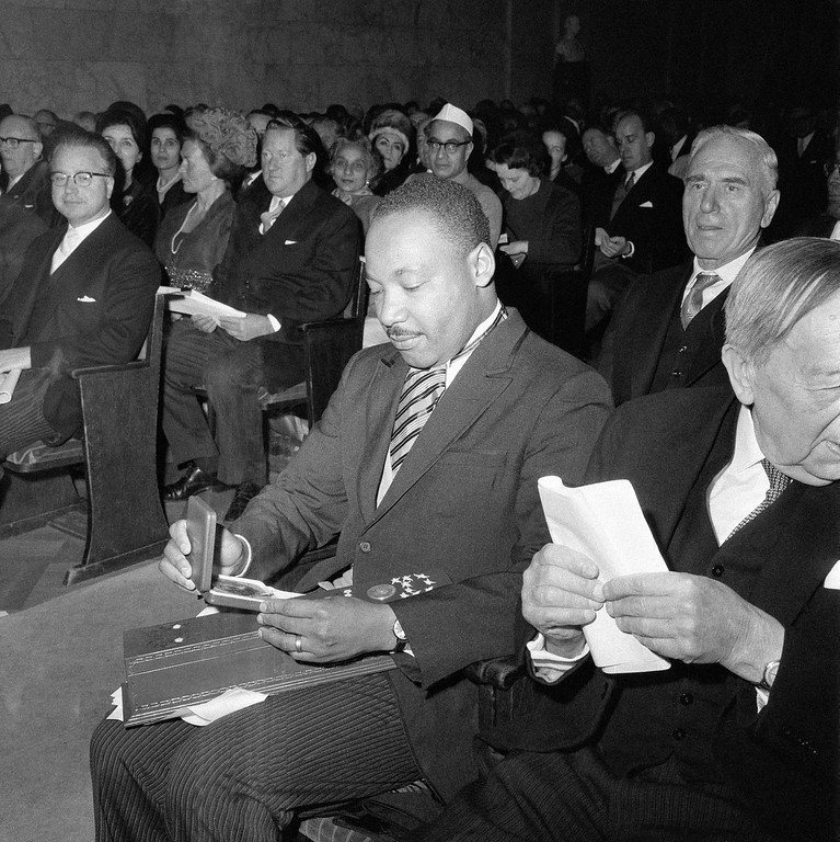 . Dr. Martin Luther King looks at his Nobel Peace Prize in Oslo, Norway, Dec. 10, 1964. (AP Photo)