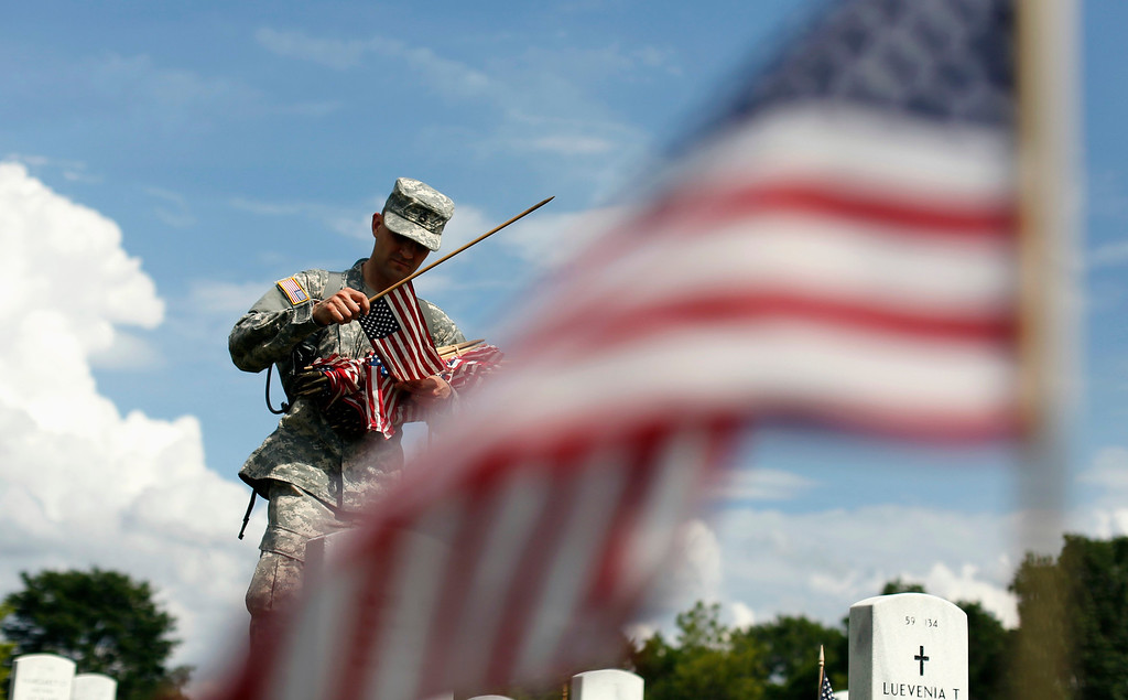 """. A soldier of the Third U.S. Infantry Regiment (The Old Guard) places a flag at a grave at Arlington National Cemetery in Virginia May 23, 2013. The annual \""""Flags-In\"""" ceremony is held in advance of Memorial Day to honor the nation\'s fallen members of the military. Flags will be placed at more than 220,000 graves.    REUTERS/Kevin Lamarque"""