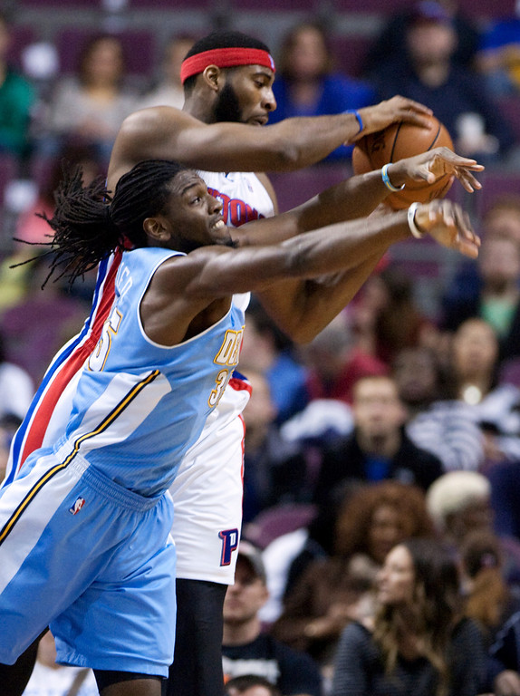 . Detroit Pistons center Andre Drummond, top, grabs a rebound away from Denver Nuggets forward Kenneth Faried during the first half of an NBA basketball game on Saturday, Feb. 8, 2014, in Auburn Hills, Mich. (AP Photo/Duane Burleson)