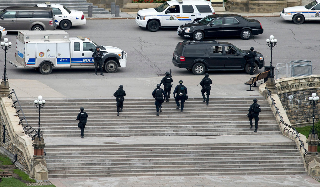 . Police teams move towards Centre Block at Parliament Hill in Ottawa on Wednesday Oct. 22, 2014.  A soldier standing guard at the National War Memorial was shot by an unknown gunman and people reported hearing gunfire inside the halls of Parliament. Prime Minister Stephen Harper was rushed away from Parliament Hill to an undisclosed location, according to officials. (AP Photo/The Canadian Press, Justin Tang)