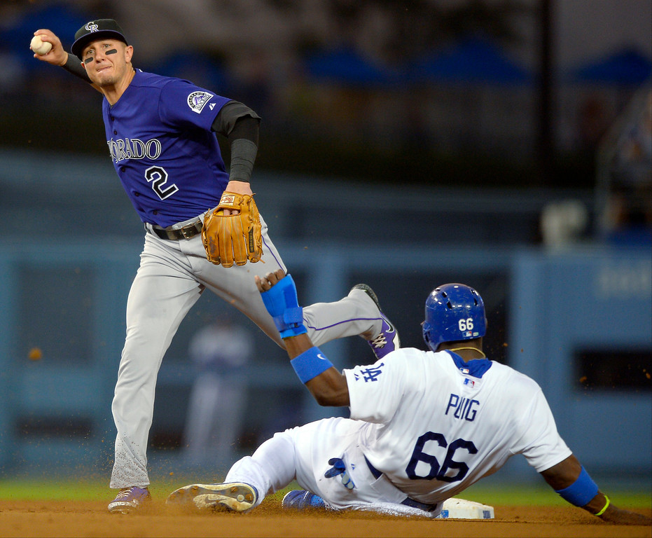 . Los Angeles Dodgers\' Yasiel Puig, right, is forced out at second as Colorado Rockies shortstop Troy Tulowitzki throws out Adrian Gonzalez at first during the third inning of a baseball game, Thursday, July 11, 2013 in Los Angeles.  (AP Photo/Mark J. Terrill)