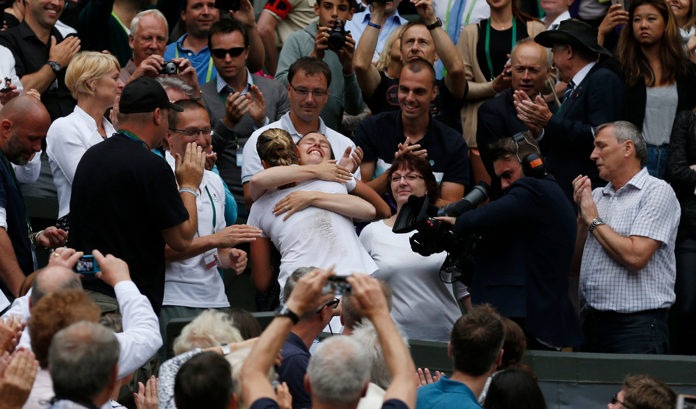 Description of . Petra Kvitova of Czech Republic embraces her family and friends in her players box as she celebrates defeating Eugenie Bouchard of Canada in their women\'s singles final at the All England Lawn Tennis Championships in Wimbledon, London, Saturday July 5, 2014. (AP Photo/Sang Tan)