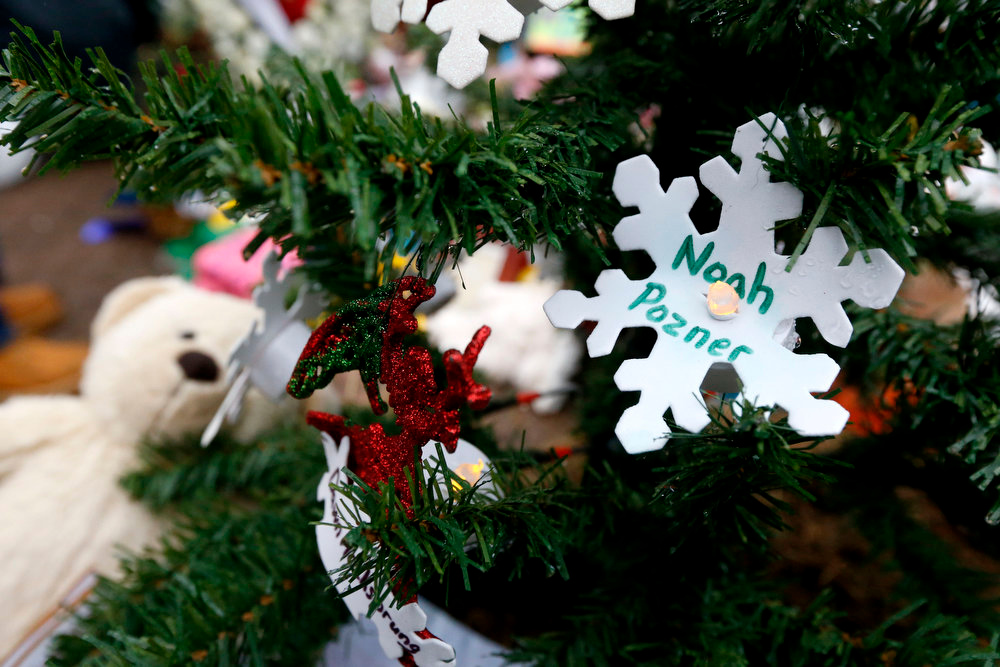 Description of . A snowflake ornament with the name of 6-year-old Noah Pozner hangs on a Christmas tree at a makeshift memorial in the Sandy Hook village of Newtown, Conn., Monday, Dec. 17, 2012, as the town mourns victims killed in Friday's school shooting. Pozner, who was killed Friday when gunman Adam Lanza opened fire inside the Sandy Hook Elementary School, will be buried Monday. (AP Photo/Julio Cortez)