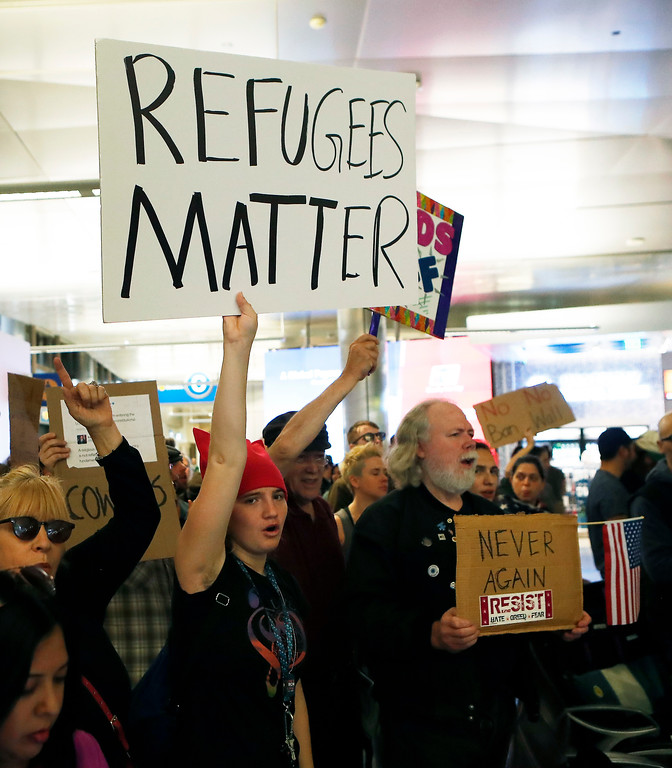 . Demonstrators hold up signs as protests against President Donald Trump\'s executive order banning travel from seven Muslim-majority countries continue at Los Angeles International Airport Sunday, Jan. 29, 2017. (AP Photo/Ryan Kang)