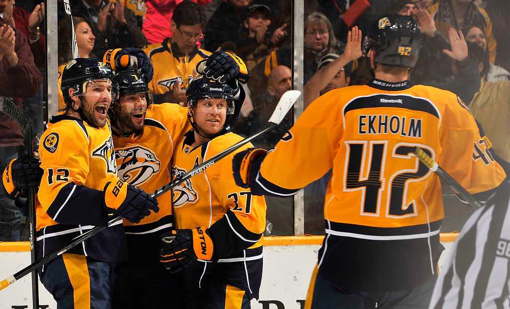 . Matt Cullen #7 of the Nashville Predators is congratulated by teammates Mike Fisher #12, Patric Hornqvist #27, and Mattias Ekholm #42 on scoring a goal against the Colorado Avalanche at Bridgestone Arena on March 25, 2014 in Nashville, Tennessee.  (Photo by Frederick Breedon/Getty Images)