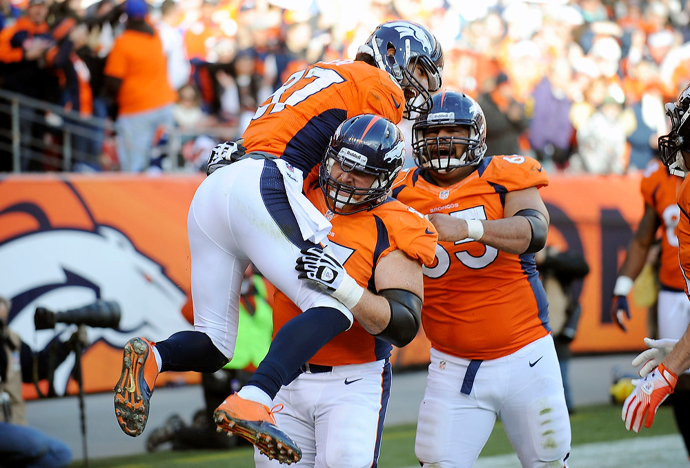 . Denver Broncos wide receiver Eric Decker gets a boost from center Dan Koppen after scoring a touchdown in the second quarter against the Cleveland Browns Sunday at Sports Authority Field. Steve Nehf, The Denver Post