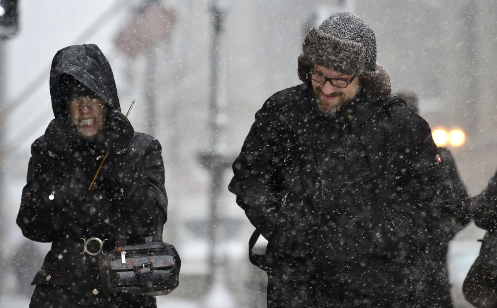 Description of . Becky Alprin (L) and Russell Flench cringe as a gust of wind hits their faces while crossing the street on March 5, 2013 in Chicago, Illinois. The worst winter storm of the season is expected to dump 7-10 inches of snow on the Chicago area with the worst expected for the evening commute.  (Photo by Brian Kersey/Getty Images)