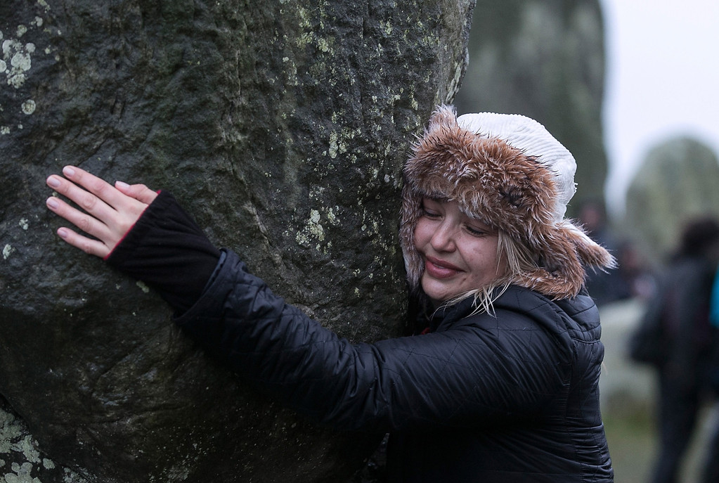 . A woman hugs the stones as druids, pagans and revellers gather, hoping to see the sun rise as they take part in a winter solstice ceremony at Stonehenge on December 21, 2013 in Wiltshire, England.   (Photo by Matt Cardy/Getty Images)