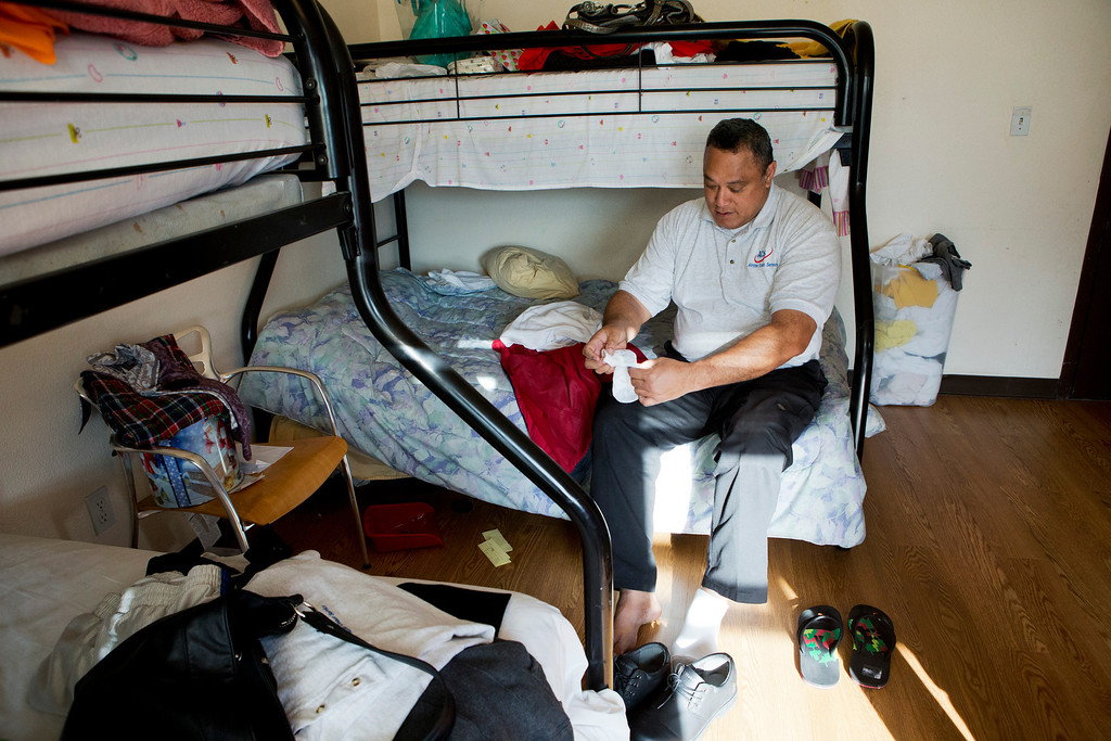 . Uatesoni Paasi gets ready for work in the InnVision Shelter Network facility where his family stays at after their house was destroyed by a December fire, in Burlingame, Calif. on Thursday, Jan. 2, 2014.  (LiPo Ching/Bay Area News Group)
