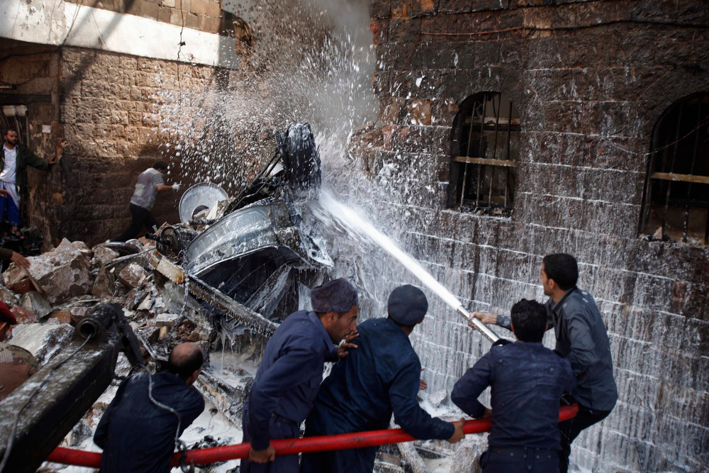 Description of . Military personnel extinguish a fire at the site of a military aircraft crash in Sanaa February 19, 2013.  A Yemeni fighter jet crashed in the centre of the capital Sanaa on Tuesday, killing at least six people, medical sources said.  REUTERS/Khaled Abdullah