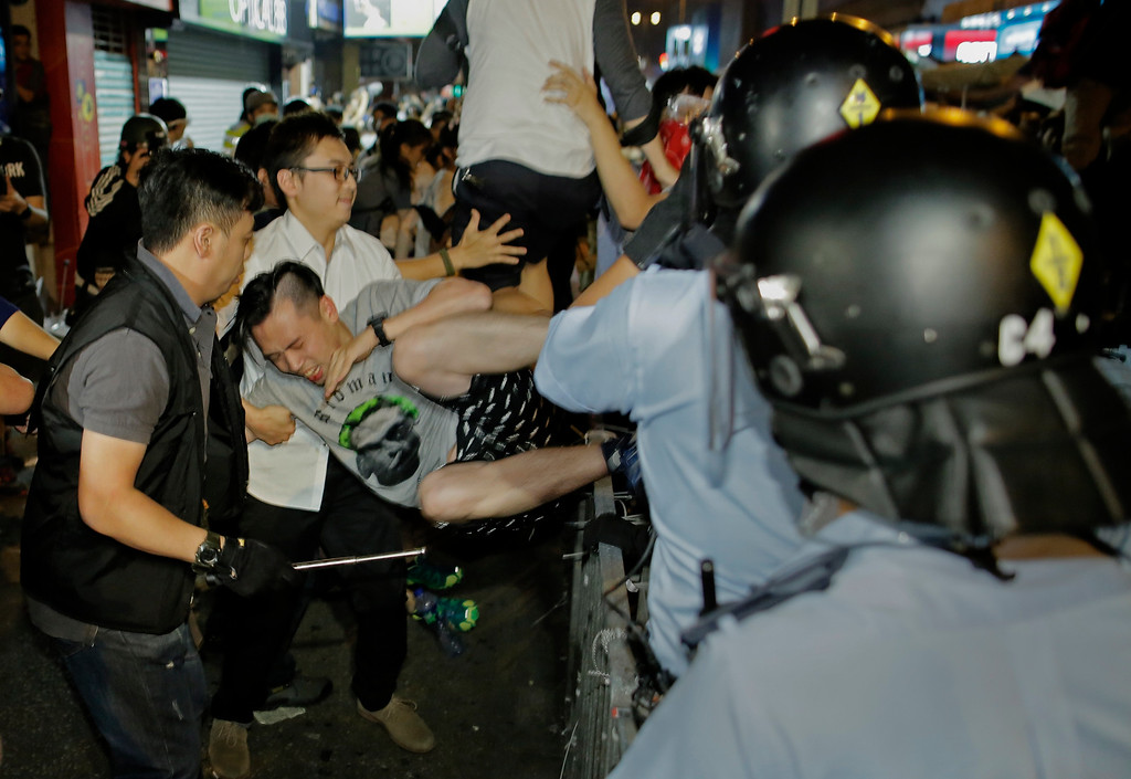 . A pro-democracy protester is taken away by police offers at an occupied section of a roadway in the Mong Kok district of Hong Kong early Sunday, Oct. 19, 2014. Hong Kong riot police battled with thousands of pro-democracy protesters for control of the city\'s streets Saturday, using pepper spray and batons to hold back defiant activists who returned to a protest zone that officers had partially cleared. (AP Photo/Vincent Yu)