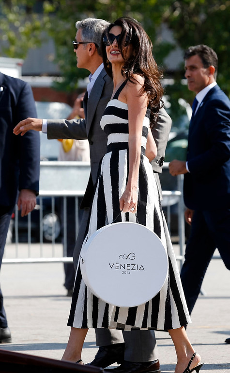 . George Clooney, left, and Amal Alamuddin arrive in Venice, Italy, Friday, Sept. 26, 2014. Clooney, 53, and Alamuddin, 36, are expected to get married this weekend in Venice, one of the world\'s most romantic settings. (AP Photo/Luca Bruno)