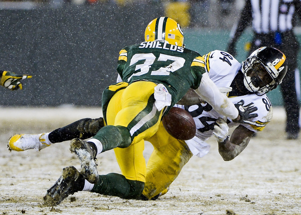 . Pittsburgh Steelers offensive player Antonio Brown (R) fails to hold onto a pass as he is tackled by Green Bay Packers defensive player Sam Shields (L) as snow falls in the second half of their NFL game at Lambeau Field in Green Bay, Wisconsin, USA, 22 December 2013. The Steelers defeated the Packers.  EPA/TANNEN MAURY