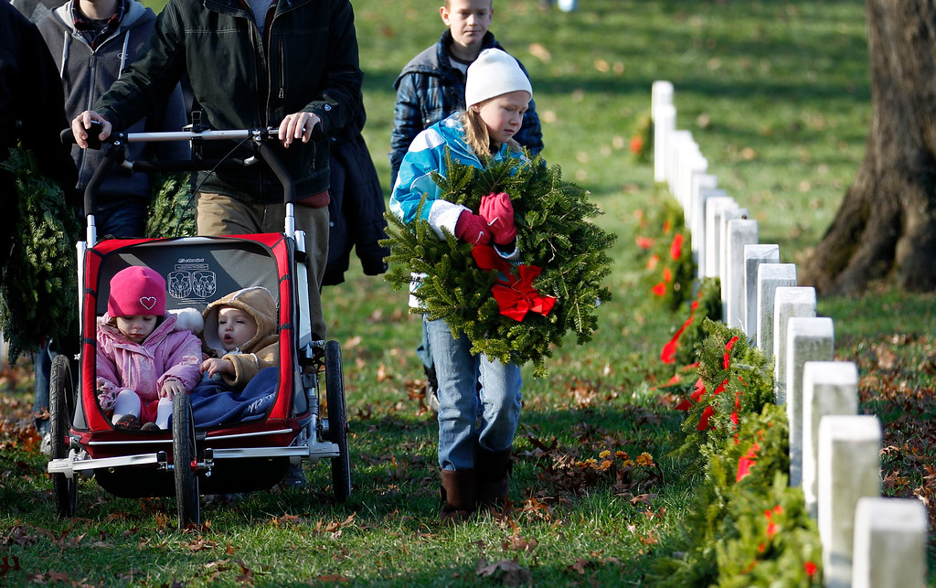 . Child volunteers help to place holiday wreaths at the graves of fallen soldiers during Wreaths Across America Day at Arlington National Cemetery on Saturday Dec. 10, 2011.  (AP Photo/Jose Luis Magana)