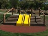 dual yellow plastic slide with timber decking clambering and hand rails