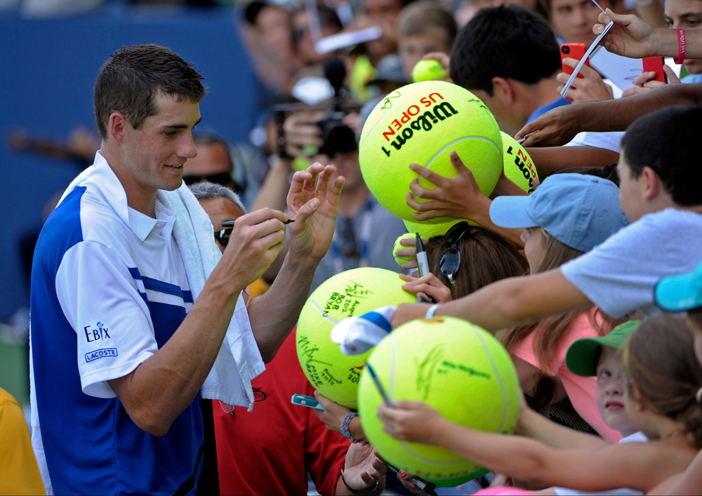 . John Isner signs autographs for fans after beating Filippo Volandri, of Italy, during the first round of the 2013 U.S. Open tennis tournament Tuesday, Aug. 27, 2013, in New York. (AP Photo/Kathy Kmonicek)