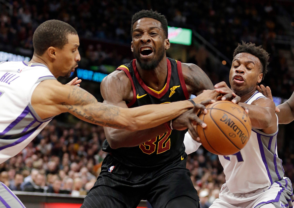 . Sacramento Kings\' George Hill, left, and Buddy Hield, from the Bahamas, knock the ball loose from Cleveland Cavaliers\' Jeff Green, center, in the first half of an NBA basketball game, Wednesday, Dec. 6, 2017, in Cleveland. The Cavaliers won 101-95. (AP Photo/Tony Dejak)