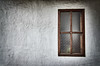 An old contrate wall painted white with a textured glass window and a dark wooden frame