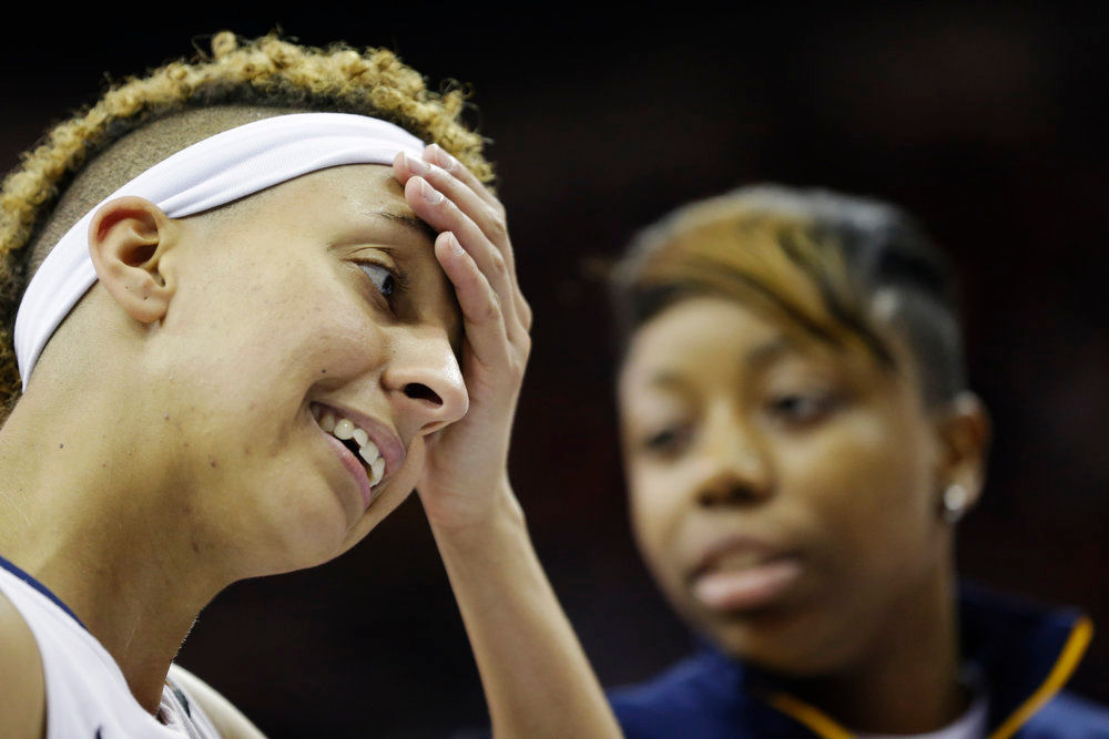 Description of . California guard Layshia Clarendon reacts after losing to Louisville at a national semifinal against California at the Women's Final Four of the NCAA college basketball tournament, Sunday, April 7, 2013, in New Orleans. Louisville won 64-57. At right is California guard Tierra Rogers. (AP Photo/Gerald Herbert)