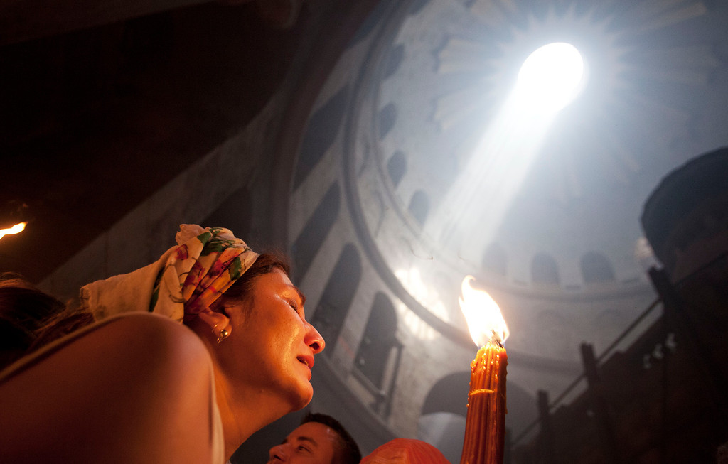 """. A Christian pilgrim holds candles at the church of the Holy Sepulcher, traditionally believed to be the burial site of Jesus Christ, during the ceremony of the Holy Fire in Jerusalem\'s Old City, Saturday, April 19, 2014. The \""""holy fire\"""" was passed among worshippers outside the Church and then taken to the Church of the Nativity in the West Bank town of Bethlehem, where tradition holds Jesus was born, and from there to other Christian communities in Israel and the West Bank. (AP Photo/Dan Balilty)"""