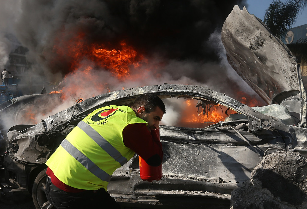 . A Hezbollah civil defense worker extinguishes a burned car at the site of an explosion near the Kuwaiti Embassy and Iran\'s cultural center, in the suburb of Beir Hassan, Beirut, Lebanon, Wednesday, Feb. 19, 2014.  (AP Photo/Hussein Malla)