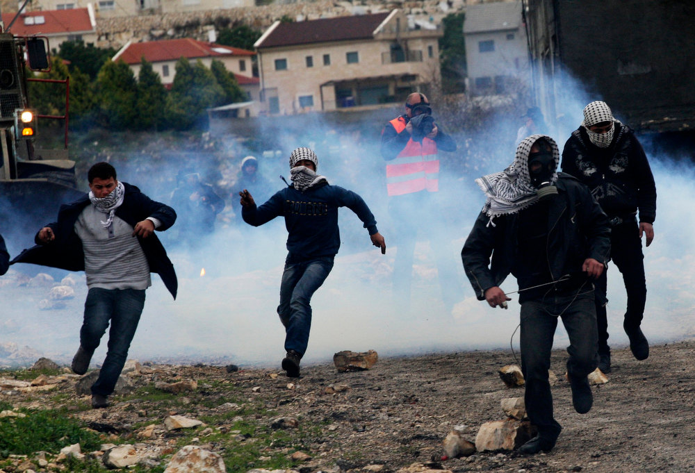 Description of . Stone-throwing Palestinian protesters run away from tear gas fired by Israeli security forces during clashes at a weekly protest against the nearby Jewish settlement of Kdumim, in the West Bank village of Kfar Kadum, near Nablus February 1, 2013. REUTERS/Abed Omar Qusini