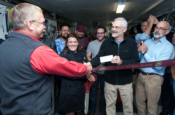 09/25/18 Wesley Bunnell | Staff Bike New Britain held a ribbon cutting at its 39 Bank St location on Tuesday afternoon. Chas LaVoie, L, presented a donation to Bike New Britain founder Cliff Parker from city employees.