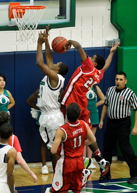 . Raiders center Elijah Sanford (25) blocked a shot from behind on Blazers\' shooter Tre Thomas (23) in the first half. The Overland High School boy\'s basketball team defeated Regis Jesuit 80-66 Tuesday night, December 11, 2012.  Karl Gehring/The Denver Post