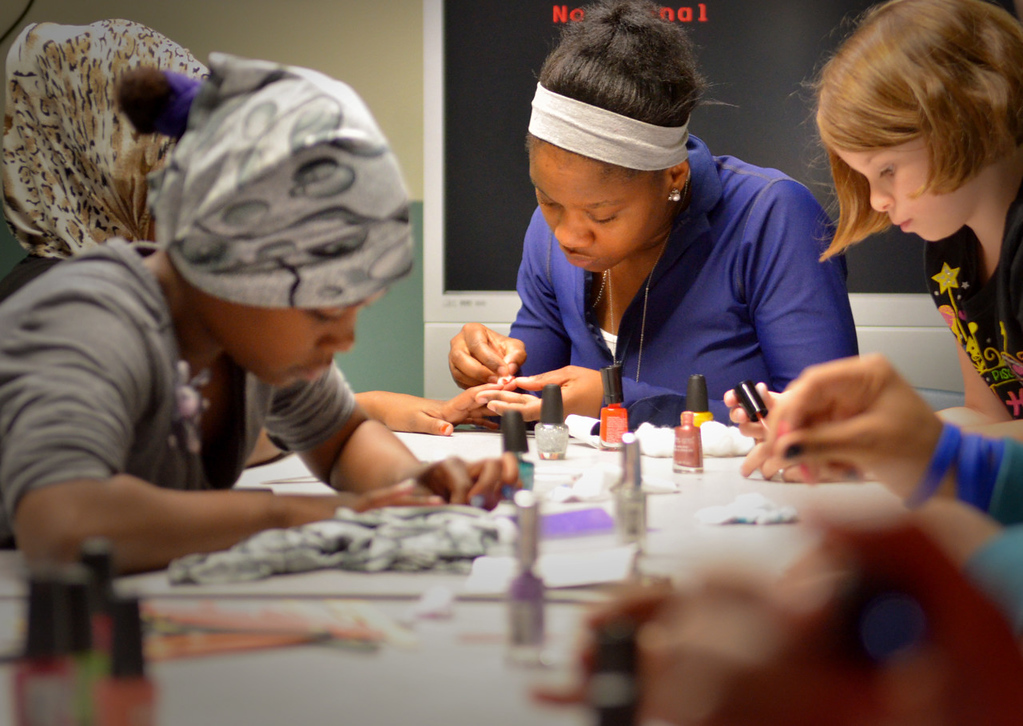 . Rika Shabazz dishes with a group of girls as they apply polish to their nails. (Pioneer Press: John Autey)