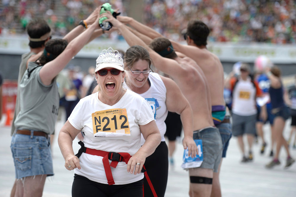 . Maureen O\'Shea-Stone cheers as she crosses the finish line in the citizen\'s race during the Bolder Boulder on Monday, May 27, in Boulder.  Jeremy Papasso/ Camera