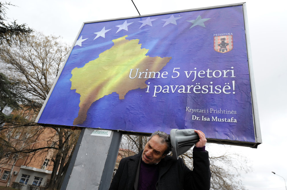 Description of . A Kosovo Albanian man stands in front of a billboard reading