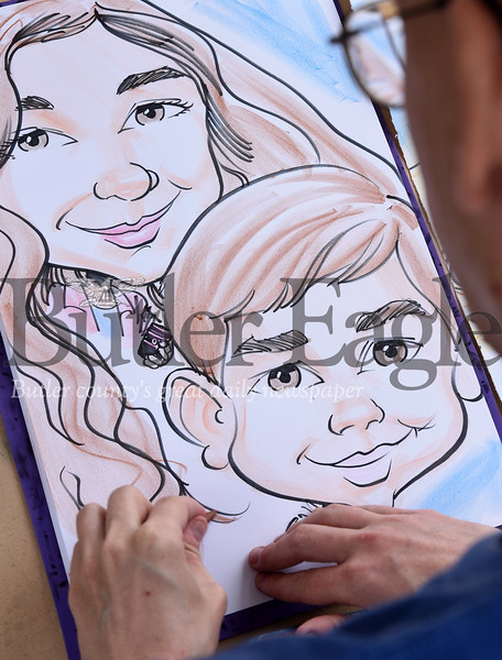 Harold Aughton/Butler Eagle: Caricatures Adam Walmsley of Cabot puts the final touches on the drawing of first cousins, Isabella Morales, 11, of Lyndora and Dekland Coburn, 6, of Butler, Saturday afternoon, at the Butler County Recovery and Resource Block Party.