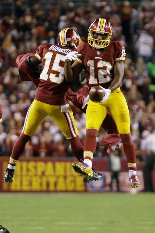. Washington Redskins wide receiver Andre Roberts (12) celebrates his touchdown with wide receiver Aldrick Robinson (15) during the first half of an NFL football game against the New York Giants in Landover, Md., Thursday, Sept. 25, 2014. (AP Photo/Patrick Semansky)