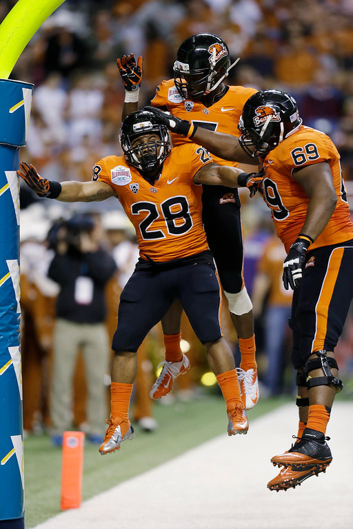. Oregon State\'s Terron Ward (28) celebrates with teammates Josh Andrews (69) and Oregon State\'s Brandin Cooks, center, after he scored a touchdown in the second quarter of the Alamo Bowl NCAA football game against Texas, Saturday, Dec. 29, 2012, in San Antonio.  (AP Photo/Eric Gay)
